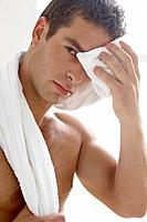 Man with towel around neck, wiping forehead