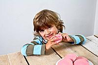 Little boy eating a pink cake