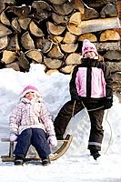 Young girls posing with sledge on snow