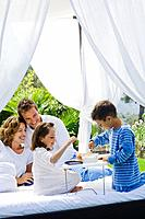 Family having breakfast on bed in garden