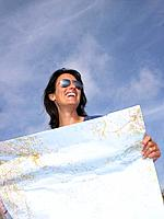 Woman looking at a map, laughing