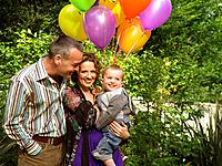 Mother, father and baby with balloons