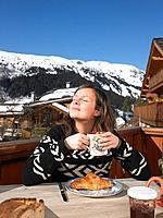 Young woman having breakfast on terrace