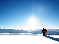 Couple walking in snow on mountain top