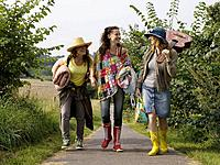 Three women walking together on path