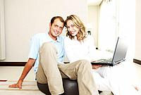 Happy couple at home with laptop