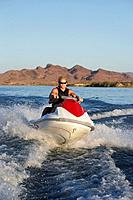 Young man riding jetski on lake