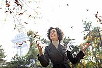 Woman outdoors with falling leaves smiling