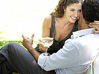 Couple outdoors with white wine embracing and smiling