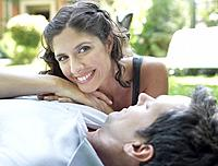 Couple outdoors lying on grass together smiling