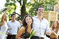 Couple outdoors at party carrying flowers and having confetti thrown at them