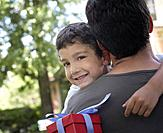 Man hugging smiling young boy holding gift outdoors