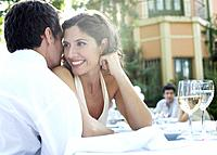 Couple at outdoor party whispering and smiling