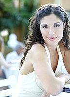 Woman at outdoor party sitting at table smiling