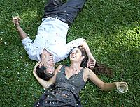 Couple outdoors lying on grass with white wine and confetti laughing