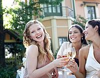 Three women at an outdoor party laughing and toasting wine
