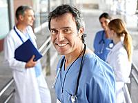 Hospital worker standing in corridor smiling with three people in background