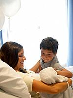 Woman holding newborn baby in hospital bed smiling while young boy watches over