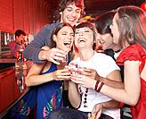 Five people with shots in nightclub toasting and smiling