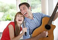 Man playing acoustic guitar indoors with woman singing into hairbrush