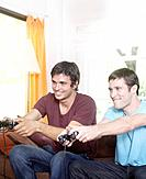 Two men playing video games in living room smiling
