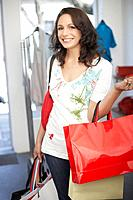 Woman in store with shopping bags smiling