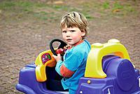 Cude blond, blue eyed boy in his colourful toy car in a farm in Cambridge, Hautapu, New Zealand