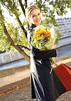 Woman outdoors with shopping bags and flowers smiling