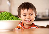Young boy in kitchen with a bowl of green peas smiling