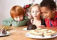 Three young kids in kitchen looking hungrily at desserts on table