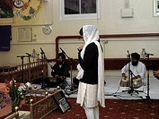 Khalsa Centre Tooting London England Girl Praying in Prayer Hall by Raggis Playing Harmonium and Tabla Drums on Anniversary of Death of Guru Tegh Baha...