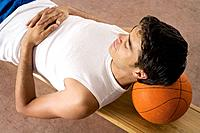 Man sleeping with his head resting on basketball