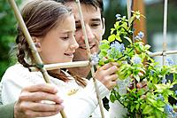 Girl and man looking at flowers twirled around wooden post