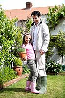 Girl standing on man´s feet while holding a pot of flowers
