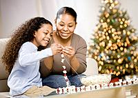 Mixed Race mother and daughter stringing popcorn garland