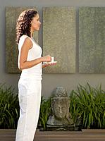 Mixed Race woman standing next to Buddha statue