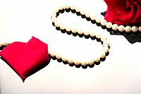 Pearl necklace beside rose and rose petal