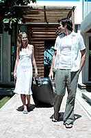Man looking at woman, woman pulling travelling bag