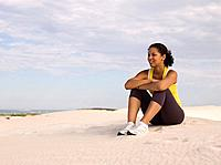 Mixed Race woman sitting on sand dune