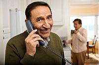 Senior Hispanic man talking on telephone