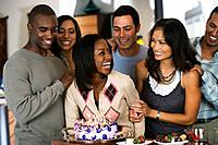 African woman celebrating birthday with multi_ethnic friends