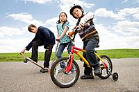 Multi_ethnic children riding skateboard, scooter and bicycle