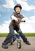 Asian boy sitting on bicycle