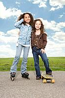 Multi_ethnic girls on roller skates and skateboard