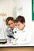 Woman assisting boy looking through the microscope
