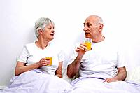 Senior man and woman enjoying orange juice