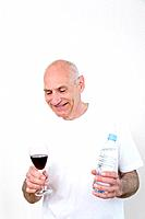 Senior man holding a glass of wine in one hand and bottled water in the other