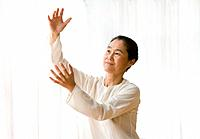 Asian woman practicing tai chi