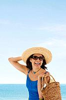 Hispanic woman wearing straw hat at beach (thumbnail)