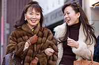 Asian mother and adult daughter laughing